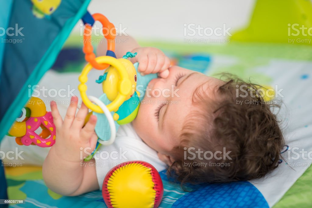 Baby boy playing with toys and biting chew toy stock photo