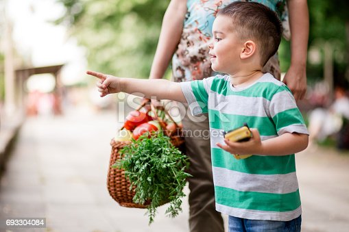 Cute Little Boy Pointing At Something He Saw, While Standing With His Mother Who Is Pregnant And Holding Basket Full Of Veggies.