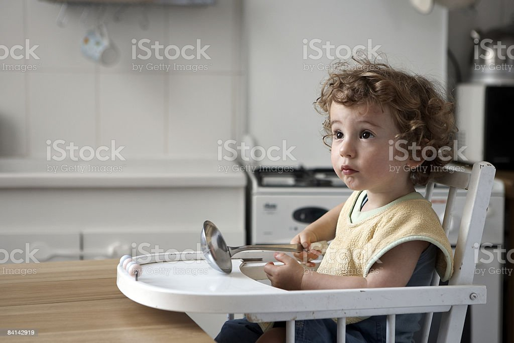baby boy sat in high chair waiting for his food royalty free stockfoto