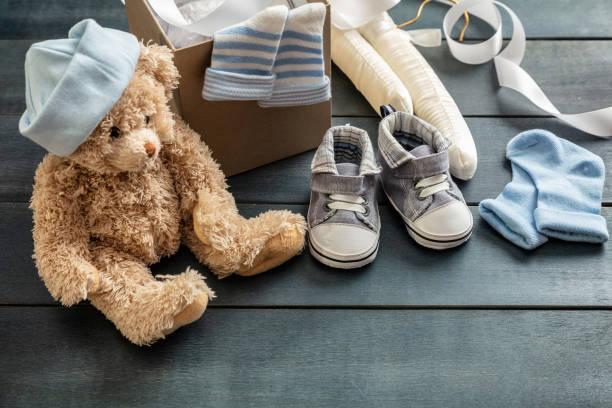 baby-jungen-schuhe und socken auf blauem hintergrund aus holz - geschenk zur taufe stock-fotos und bilder
