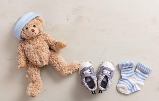 baby-jungen-schuhe und socken auf hölzernen hintergrund - geschenk zur taufe stock-fotos und bilder