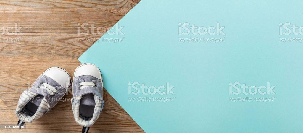 Chaussures de garçon de bébé sur fond bleu et bois pastel bannière - Photo