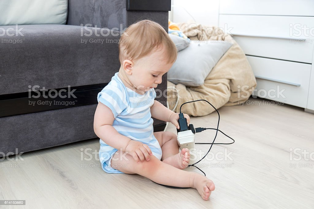 Baby boy sitting alone and playing with electrical cables – Foto