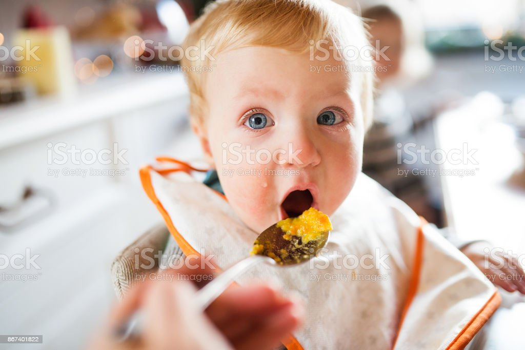 Baby boy sitting in highchair eating stock photo