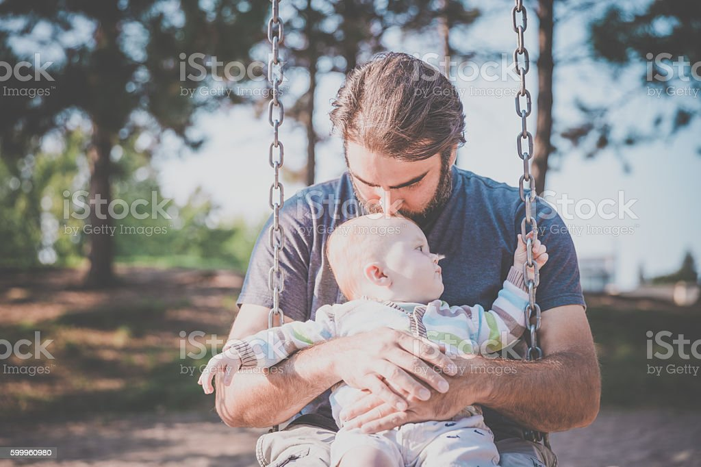 Baby Boy Sitting in Playground Swing Outdoors with Dad stock photo