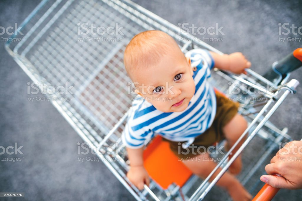 Baby boy sitting in the shopping trolley outside. - foto stock