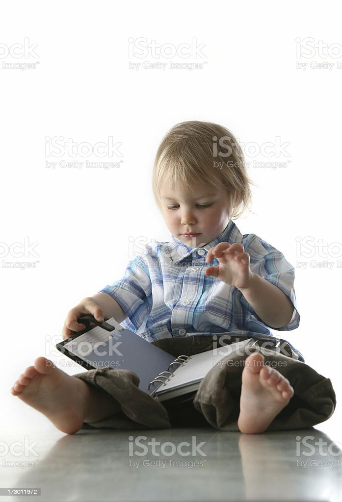 Baby boy sitting on floor with planner on lap royalty-free stock photo