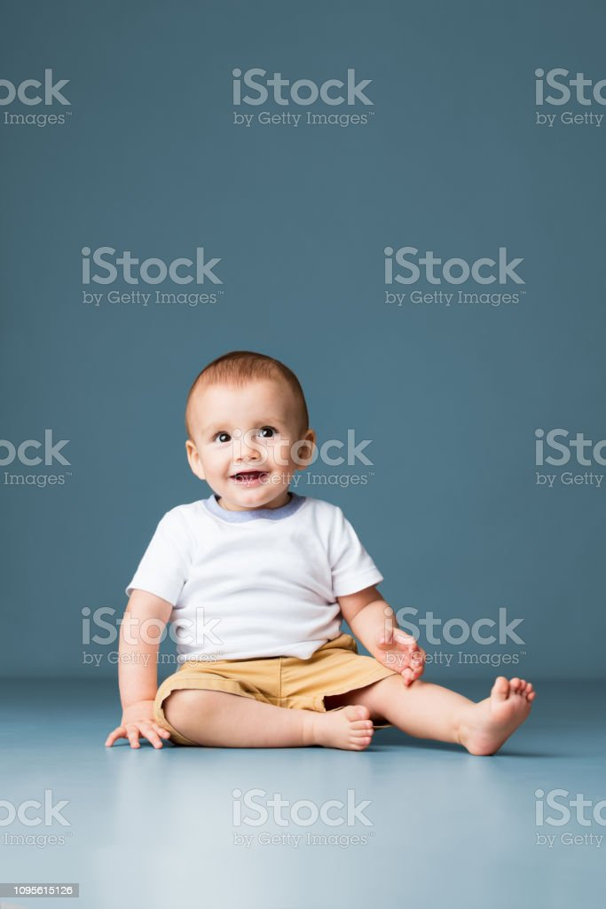 A latin baby boy sitting on the floor barefoot and smiling at camera.