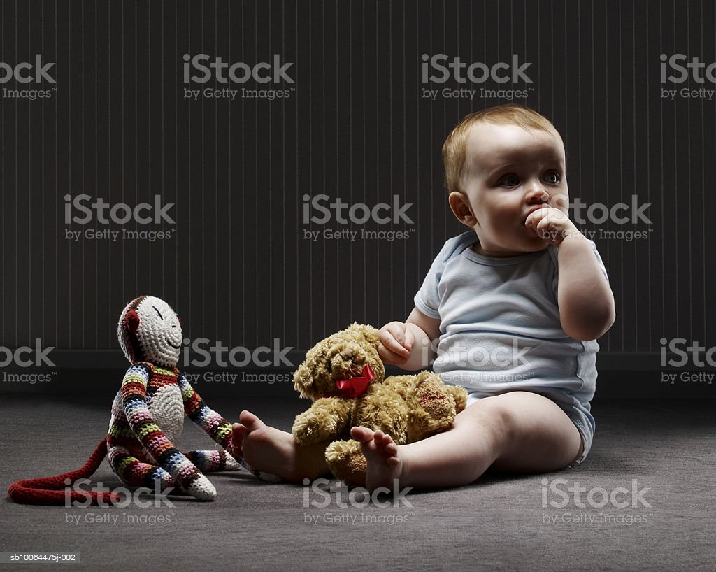 Baby boy (9-12 months) sitting with soft toys on floor Lizenzfreies stock-foto