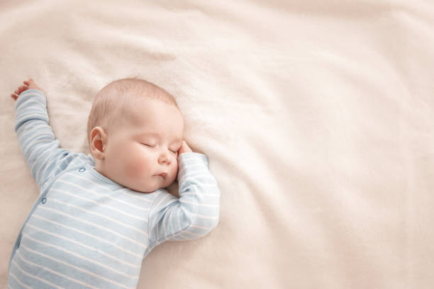 Baby boy sleeping covered with soft blanket stock photo