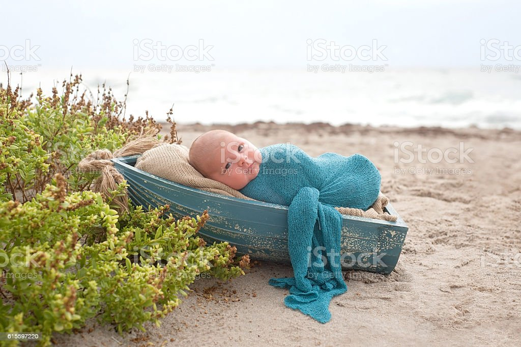 Baby Boy Sleeping in a Tiny Boat stock photo