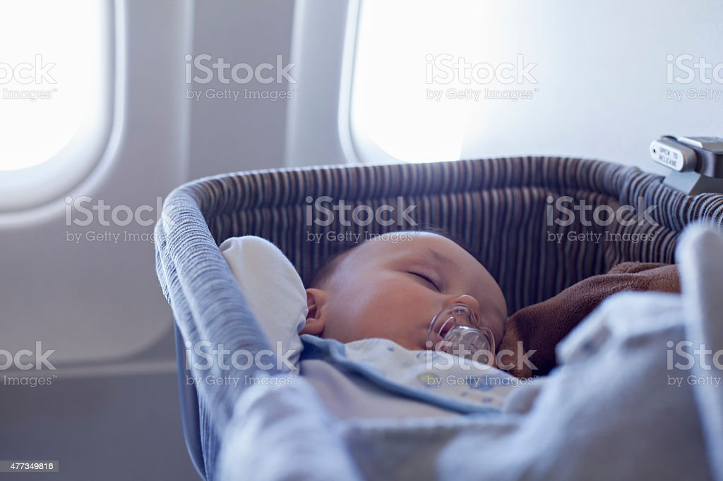 Baby Boy Sleeping In Bassinet On Airplane stock photo