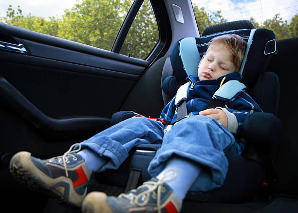 petit garçon dormant dans un siège de voiture - child car sleep photos et images de collection