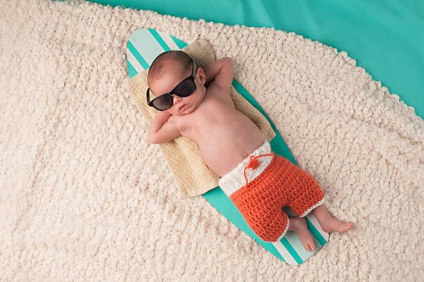 Baby Boy Sleeping on a Surfboard stock photo