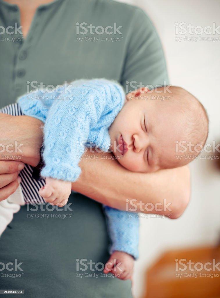 Baby boy sleeping on Dad's arm stock photo