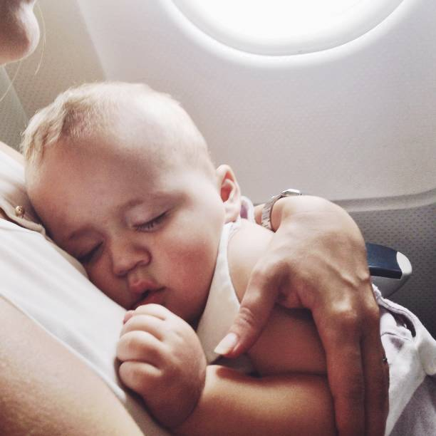 Baby boy sleeping on mother's lap in an airplane stock photo