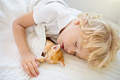 istock Baby boy sleeping with kitten. Child and cat. 1272105142