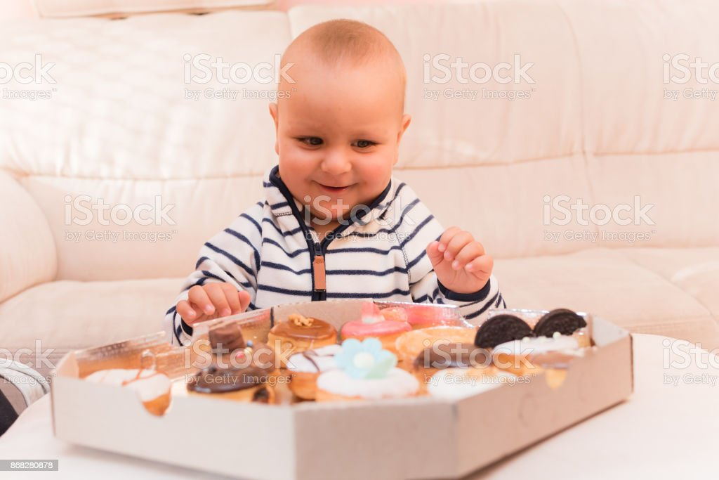 Baby boy smile when he see donuts on the table stock photo