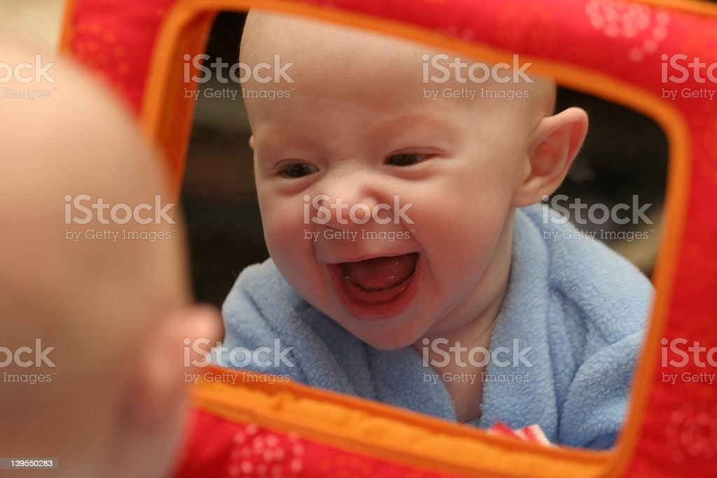 Baby boy smiling at his reflection in a toy mirror royalty-free stock photo