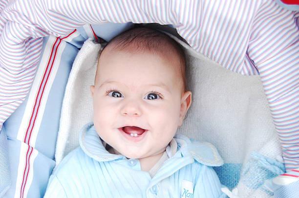 baby boy smiling up out of pram - baby teeth stok fotoğraflar ve resimler