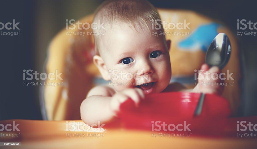 baby boy spoon eats itself stock photo