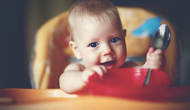 baby boy spoon eats itself - kinderstuhl und tisch stock-fotos und bilder