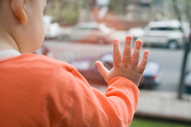 Baby Boy Standing By Window Baby Boy looking Outside By Window boy looking out window stock pictures, royalty-free photos & images