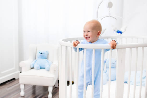 Baby boy standing in bed in white nursery stock photo