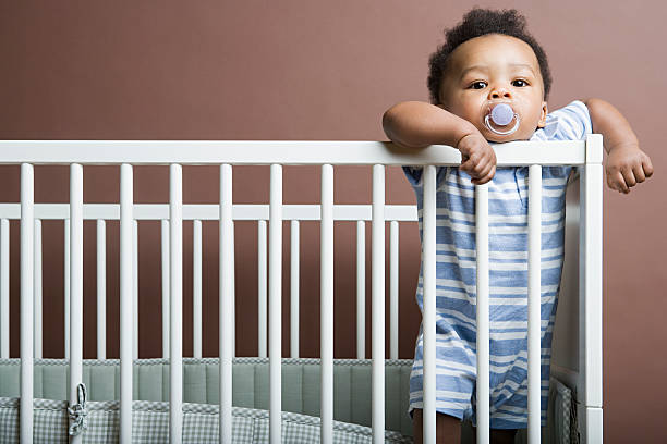 Baby boy standing in cot stock photo