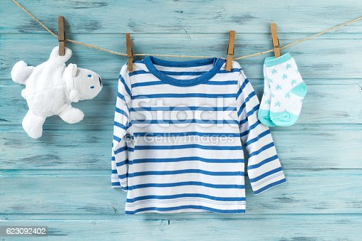 istock Baby boy striped shirt, socks and white toy bear 623092402
