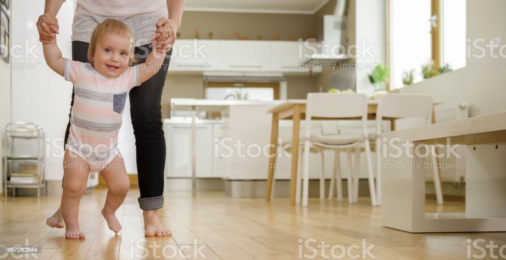 Baby boy taking first steps stock photo