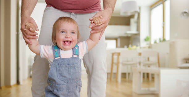 Baby boy taking first steps Baby boy taking his first steps on wooden floor with help of his father. bib overalls boy stock pictures, royalty-free photos & images