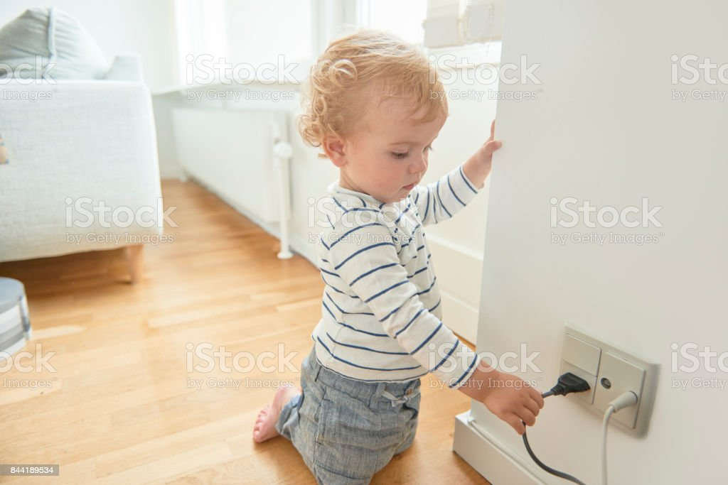 Baby boy touching electrical plug in the wall. stock photo