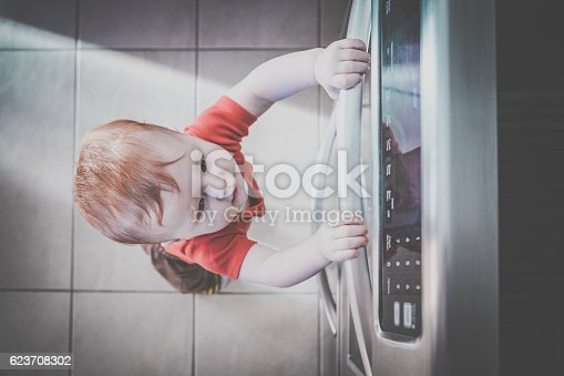 istock Baby Boy Touching Grabbing Oven Handle in Kitchen 623708302