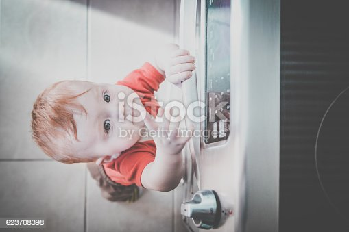 istock Baby Boy Touching Grabbing Oven Handle in Kitchen 623708398