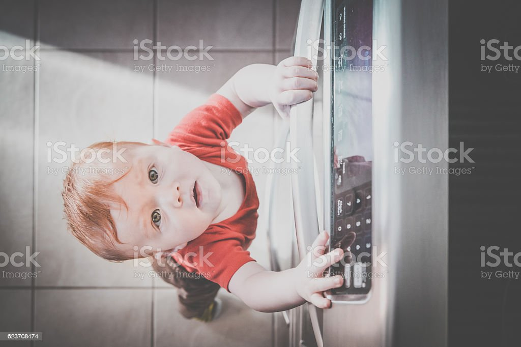 Baby Boy Touching Grabbing Oven Handle in Kitchen stock photo