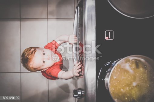 istock Baby Boy Touching Grabbing Oven Handle in Kitchen 629129120