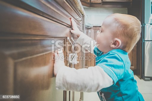 Young Baby Boy touching and or Grabbing Locked Cabinet Handle in modern Kitchen, The baby boy is almost walking on his own and trying to grab everything.