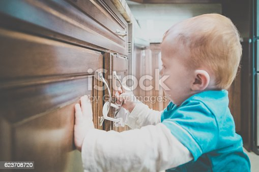 istock Baby Boy Touching Locked Cabinet Handle in Kitchen 623708720