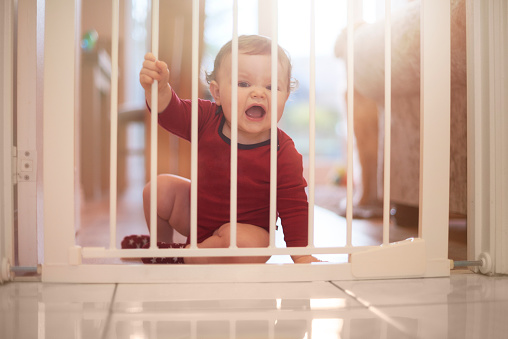 Baby boy holds on to the baby gate and crying to get out.