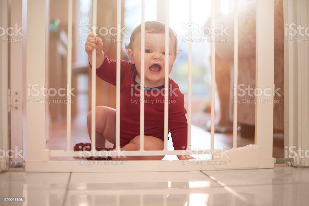 Baby boy upset at the baby gate stock photo