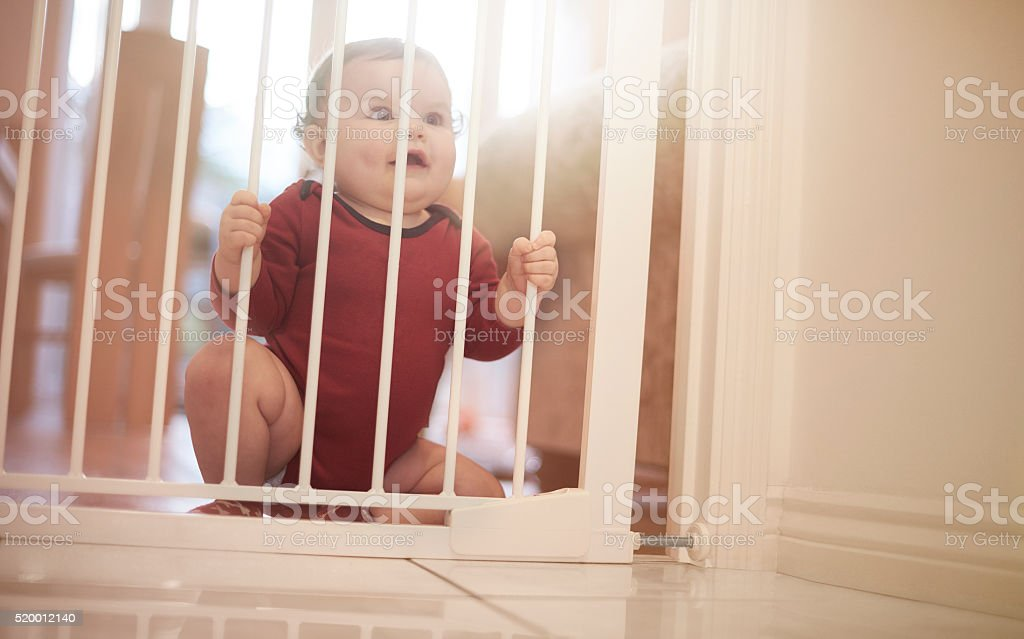 Baby boy waits behind baby gate stock photo