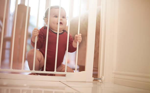 Baby boy waits behind baby gate stock photo