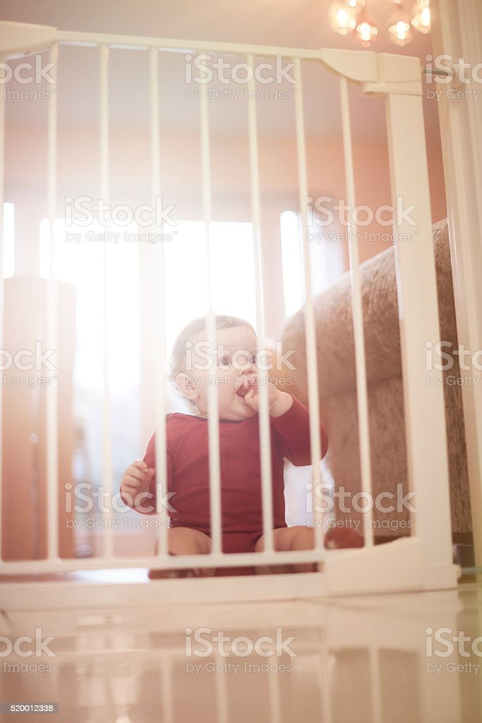 Baby boy waits patiently behind baby safety gate stock photo