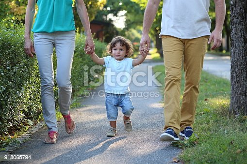 Baby boy walking with parents