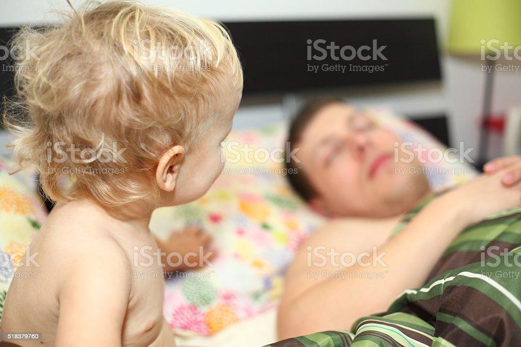 Baby boy watching his dad sleeping stock photo
