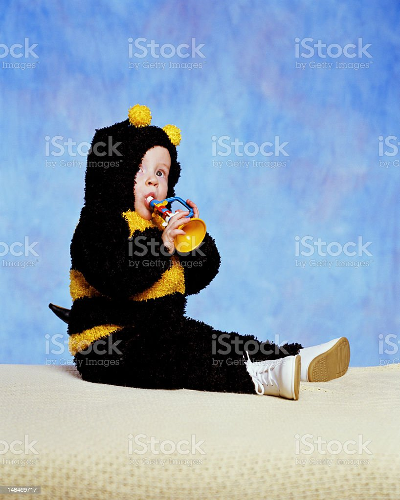 Baby boy (12-15 months) wearing bumblebee costume, playing toy h royalty-free stock photo