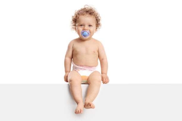 Baby boy with a pacifier sitting on a panel stock photo