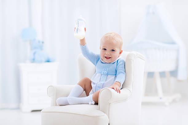 Baby boy with bottle drinking milk or formula stock photo