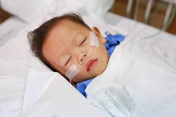 Baby boy with breathing tube in nose receiving medical treatment. Intensive care at hospital. stock photo